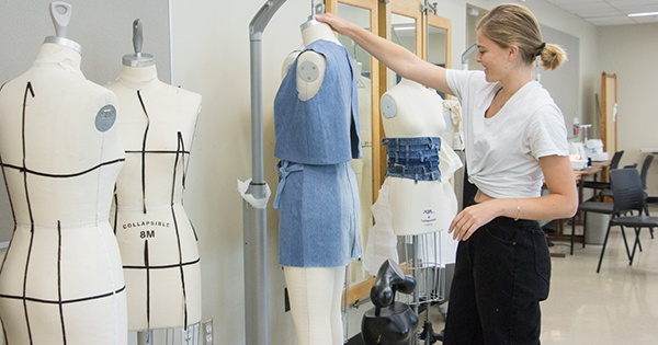 Morgan Young works with her designs on a mannequin.